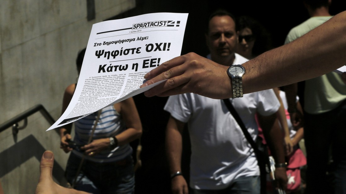 "A man passes out a leaflet reading in Greek ""Vote NO in the referendum, Down with the EU"" to a passerby, outside of the Metro station in Syntagma square in central Athens, on Thursday, July 2, 2015. Greece braced for more chaos on the streets outside its mostly shuttered banks Thursday, as Athens and its creditors halted talks on resolving the country's deepening financial crisis until a referendum this weekend. (AP Photo/Petros Karadjias)"